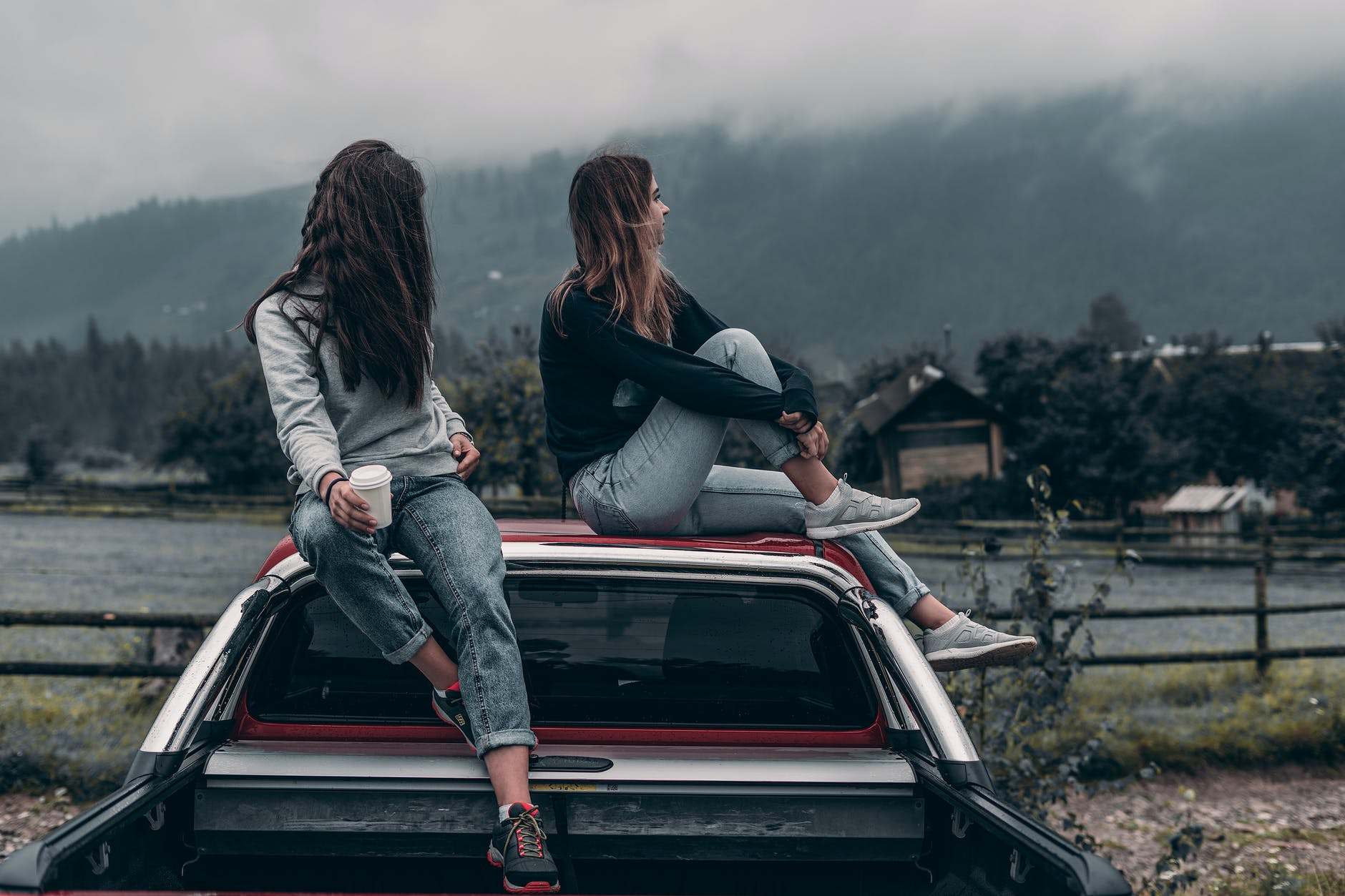 two women sitting on vehicle roofs